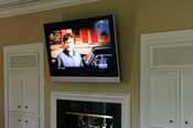TV mounted above the fireplace in the master bedroom. Expertly installed by HiFi Doc